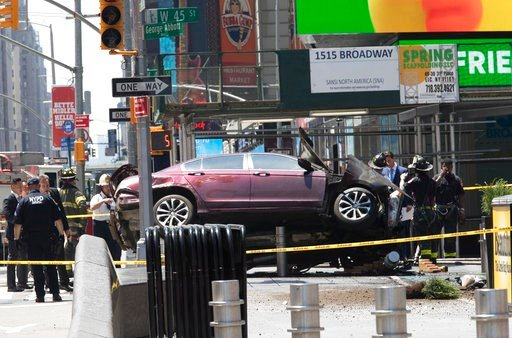 (AP Photo/Mary Altaffer). A car rests on a security barrier in New York's Times Square after driving through a crowd of pedestrians, injuring at least a dozen people, Thursday, May 18, 2017.