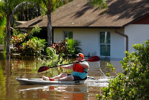 (AP Photo/Chris O'Meara). A man paddles a kayak near a flooded home along the Alafia River Tuesday, Sept. 12, 2017, in Lithia, Fla. A storm surge from Hurricane Irma pushed water into the low lying area.