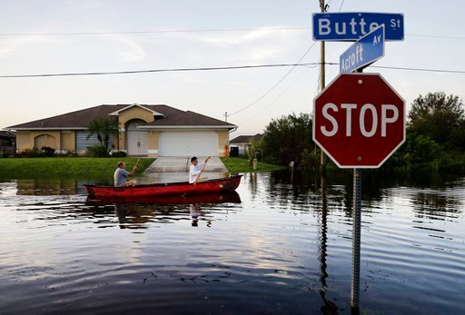 (AP Photo/David Goldman). Pierre Ghantos, left, and his son Nathan paddle though their flooded neighborhood in the aftermath of Hurricane Irma in Fort Myers, Fla., Tuesday, Sept. 12, 2017.