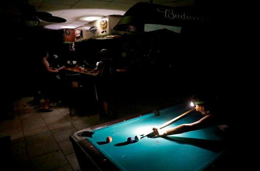 (AP Photo/David Goldman). Lisa Borruso plays pool using a headlamp as the power remains out following Hurricane Irma at Gators' Crossroads in Naples, Fla., Monday, Sept. 11, 2017. Statewide, an estimated 13 million people, or two-thirds of Florida's po...