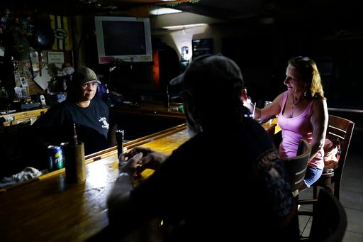 (AP Photo/David Goldman). Linda Pauly, from left, David Fowkes and Lisa Borruso gather at Gators' Crossroads as the power remains out following Hurricane Irma in Naples, Fla., Monday, Sept. 11, 2017. Statewide, an estimated 13 million people, or two-th...