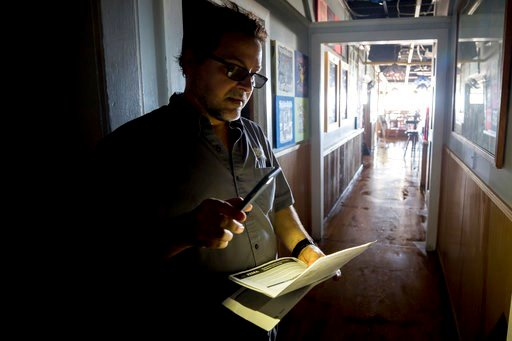 (AP Photo/Stephen B. Morton). John Yarbrough, the owner of Spanky's restaurant on Tybee Island, Ga., uses the light from his cellphone to read paperwork, Tuesday, Sept. 12, 2017, after storm surge from Tropical Storm Irma knocked out power and flooded ...