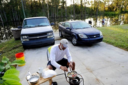 (AP Photo/David Goldman). Cesar De La Cruz makes breakfast on a propane stove in his driveway as his neighborhood is flooded from Hurricane Irma in Fort Myers, Fla., Tuesday, Sept. 12, 2017. Millions statewide remained without power and officials warne...