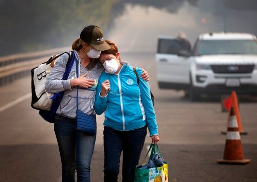 (Randy Pench /The Sacramento Bee via AP). Colby Clark of San Francisco, left, comforts her mother, Bonnie Trexler, after being escorted by law enforcement to her home in Silverado Highland to retrieve medicine and some personal items on Wednesday, Oct....