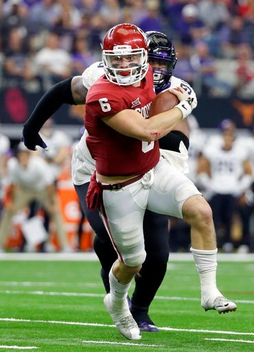 (AP Photo/Tony Gutierrez). Oklahoma quarterback Baker Mayfield, front, is chased out of the pocket by TCU defensive tackle Ross Blacklock, rear, in the second half of the Big 12 Conference championship NCAA college football game, Saturday, Dec. 2, 2017...