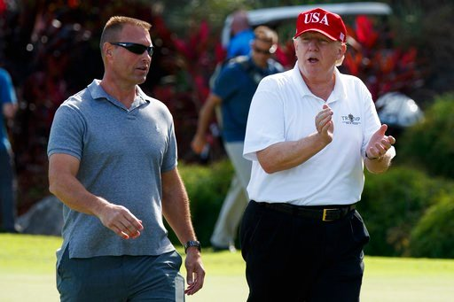 (AP Photo/Evan Vucci, File). FILE - In this Friday, Dec. 29, 2017 file photo, President Donald Trump walks with Gene Gibson, commanding officer at Coast Guard Station Lake Worth Inlet, as he arrives to meet with members of the U.S. Coast Guard, who he ...