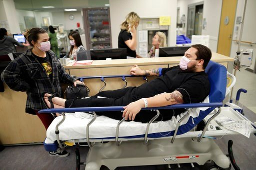 (AP Photo/Gregory Bull). Donnie Cardenas, right, waits in an emergency room hallway alongside roommate Torrey Jewett, left, as he recovers from the flu at the Palomar Medical Center in Escondido, Calif., on Wednesday, Jan. 10, 2018. The San Diego Count...
