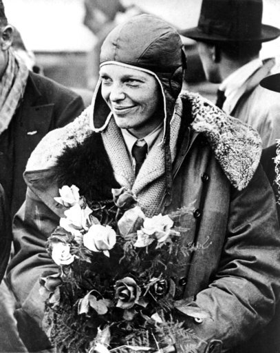 """(AP Photo, File). FILE - In a June 26, 1928 file photo, American aviatrix Amelia Earhart poses with flowers as she arrives in Southampton, England, after her transatlantic flight on the """"Friendship"""" from Burry Point, Wales. Bones found in 1940 on a wes..."""