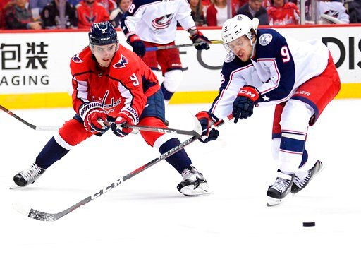 (AP Photo/Nick Wass). Washington Capitals defenseman Dmitry Orlov, left, of Russia, fights for the puck against Columbus Blue Jackets left wing Artemi Panarin, of Russia, during the second period in Game 1 of an NHL first-round hockey playoff series Th...