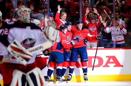 (AP Photo/Nick Wass). Washington Capitals center Evgeny Kuznetsov, second from right, celebrates his goal with John Carlson (74) and T.J. Oshie (77) during the first period in Game 1 of an NHL first-round hockey playoff series against the Columbus Blue...