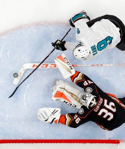 (AP Photo/Reed Saxon). San Jose Sharks left wing Evander Kane, top, scores past Anaheim Ducks goaltender John Gibson during the second period of Game 1 of an NHL hockey first-round playoff series in Anaheim, Calif., Thursday, April 12, 2018.
