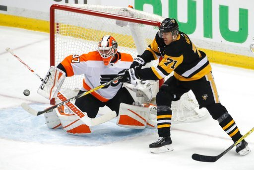 (AP Photo/Gene J. Puskar). Pittsburgh Penguins' Evgeni Malkin (71) cannot get his stick on a puck in front of Philadelphia Flyers goaltender Brian Elliott (37) during the first period in Game 2 of an NHL first-round hockey playoff series in Pittsburgh,...