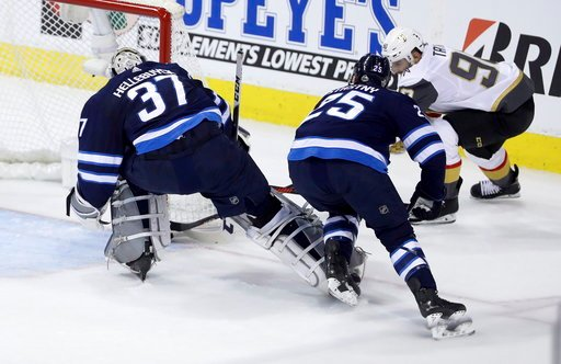 (Trevor Hagan/The Canadian Press via AP). Las Vegas Golden Knights' Tomas Tatar (90) scores on Winnipeg Jets goaltender Connor Hellebuyck (37) with Paul Stastny (25) in front of the net during first period game 2 NHL Western Conference Finals hockey ac...
