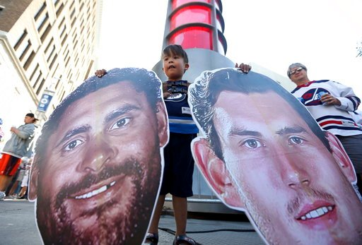 (Trevor Hagan/The Canadian Press via AP). Conway, 4, from Winnipeg, holds large heads from Winnipeg Jets' Dustin Byfuglien (33) and goaltender Connor Hellebuyck (37) as fans take part in the White Out Street Party, outside the Bell MTS Place, prior to ...