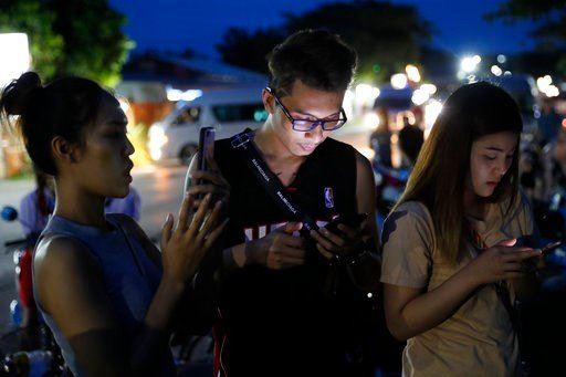 (AP Photo/Vincent Thian). People check their mobile phones for update while waiting at a military airbase during emergency helicopter evacuation in Chiang Rai province, northern Thailand, Monday, July 9, 2018. Four more of the boys trapped for over two...